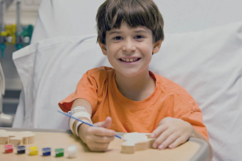 Pre-teen boy does crafts from a hospital bed.