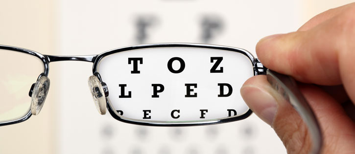 Eye glasses are held in front of an eye test chart.